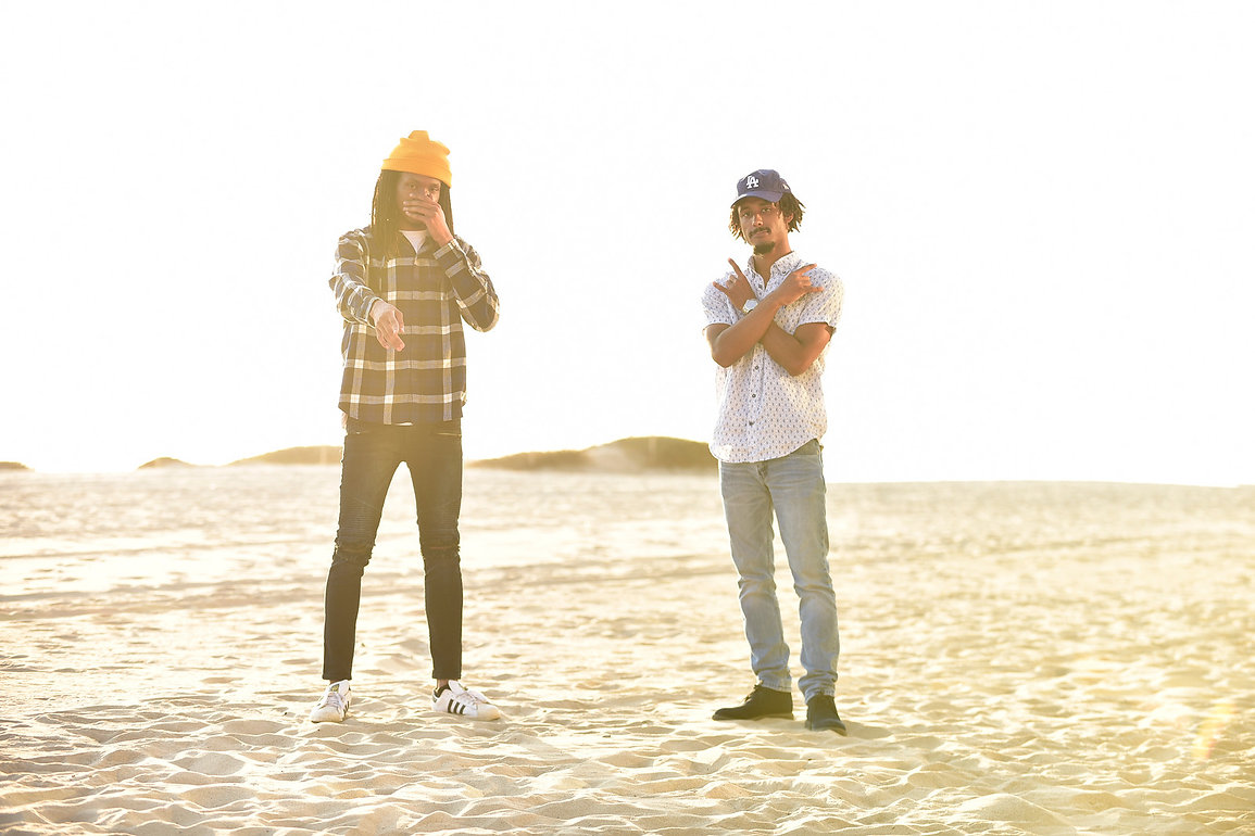 LXRYCLVB recording artists Shallah Hendrix (L) and Keenan Mills stand on a sandy beach