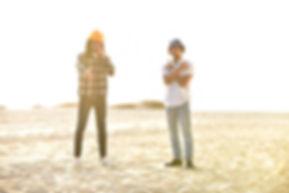 LXRYCLVB recording artists Shallah Hendrix (L) and Keenan Mills stand on a sandy beach