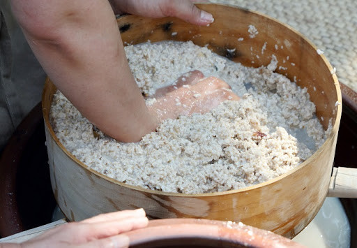 Filtering makgeolli by hand is the traditional way to separate the alcohol from the rice sediment