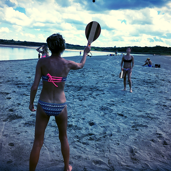 Girls playing frescobol beach paddleball with Capri Frescobol beach paddleball sets.