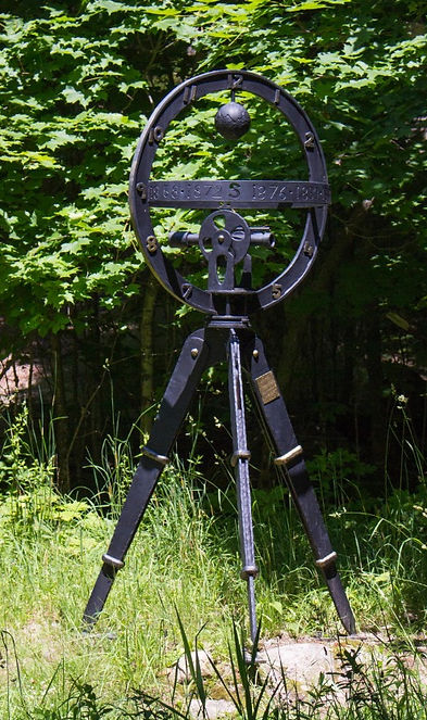 A steel and bronze surveyor's tripod with symbols of time and direction and dates.