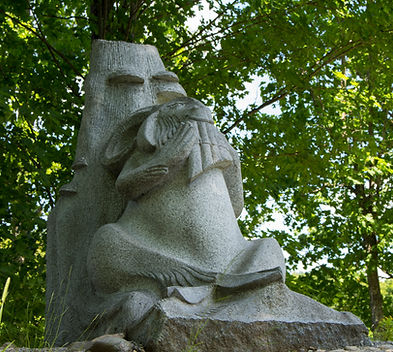 A large salt and pepper granite sculpture of the Greek god Pan resting against a tree stump while playing his pan pipes.