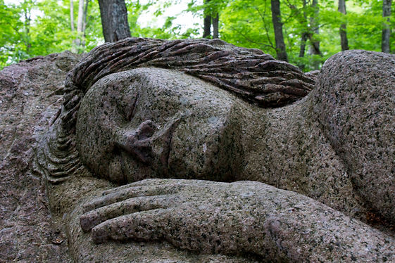 A granite stone sculpture of a woman sleeping on a large rock.