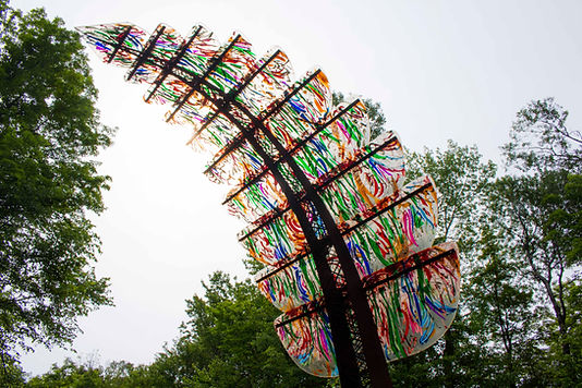 A 14 foot tall leaf-shaped sculpture with a stem made of steel and leaves made of colourful acrylic panels.