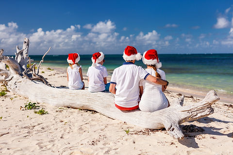 Family with Christmas hats on the beach
