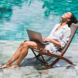 Woman working with laptop by the pool. F