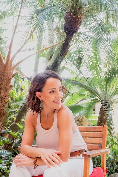 Mujer sentada sonrriendo con fondo de palmeras