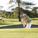 Man teaching a woman how to play golf.jp