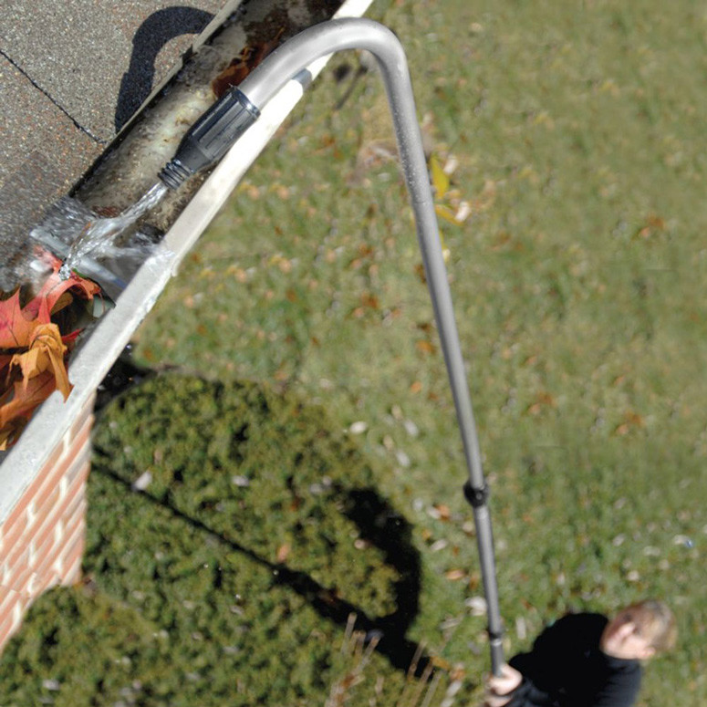Cleaning gutter with garden hose attachment.