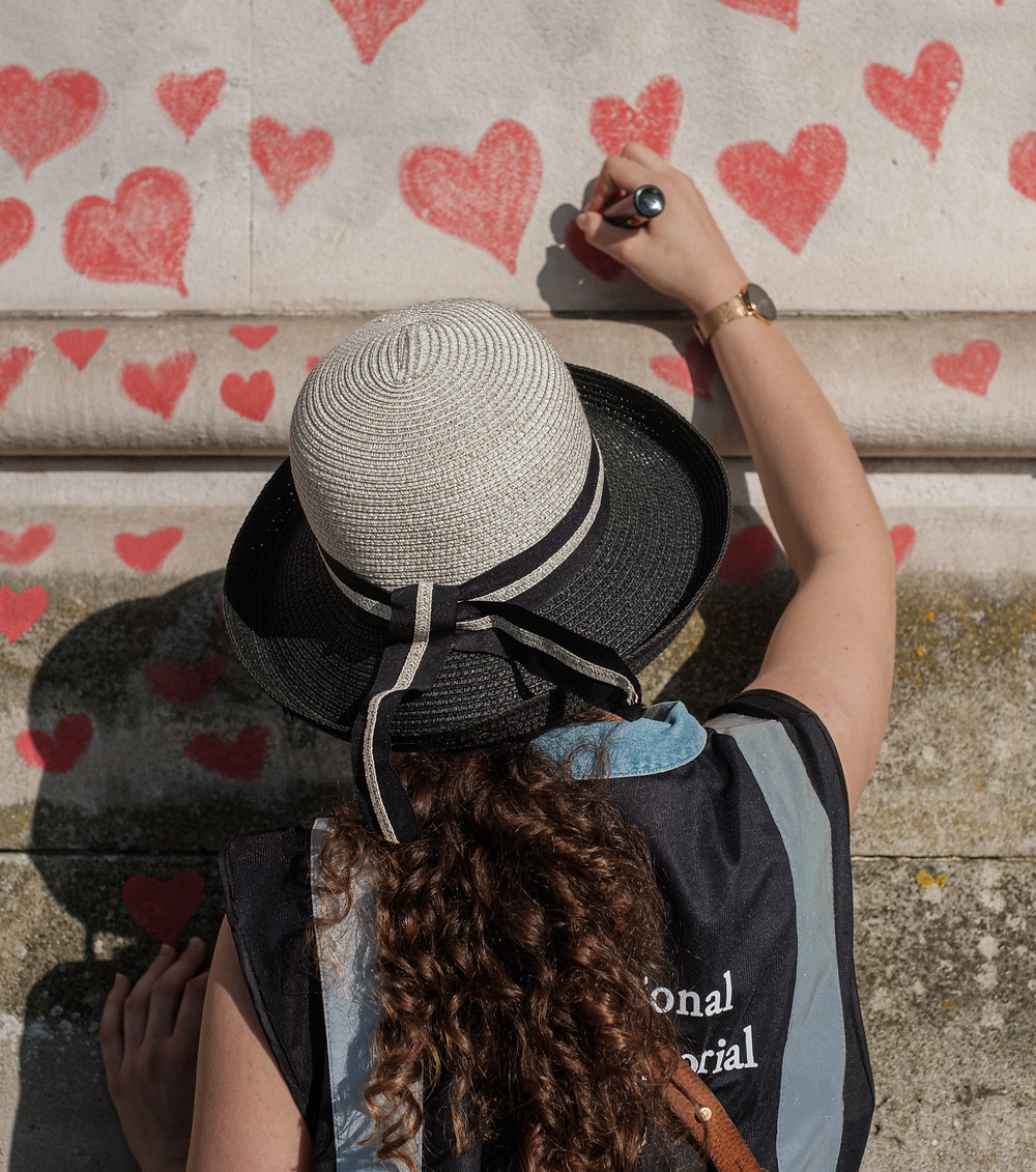 A girl drawing hearts on a wall