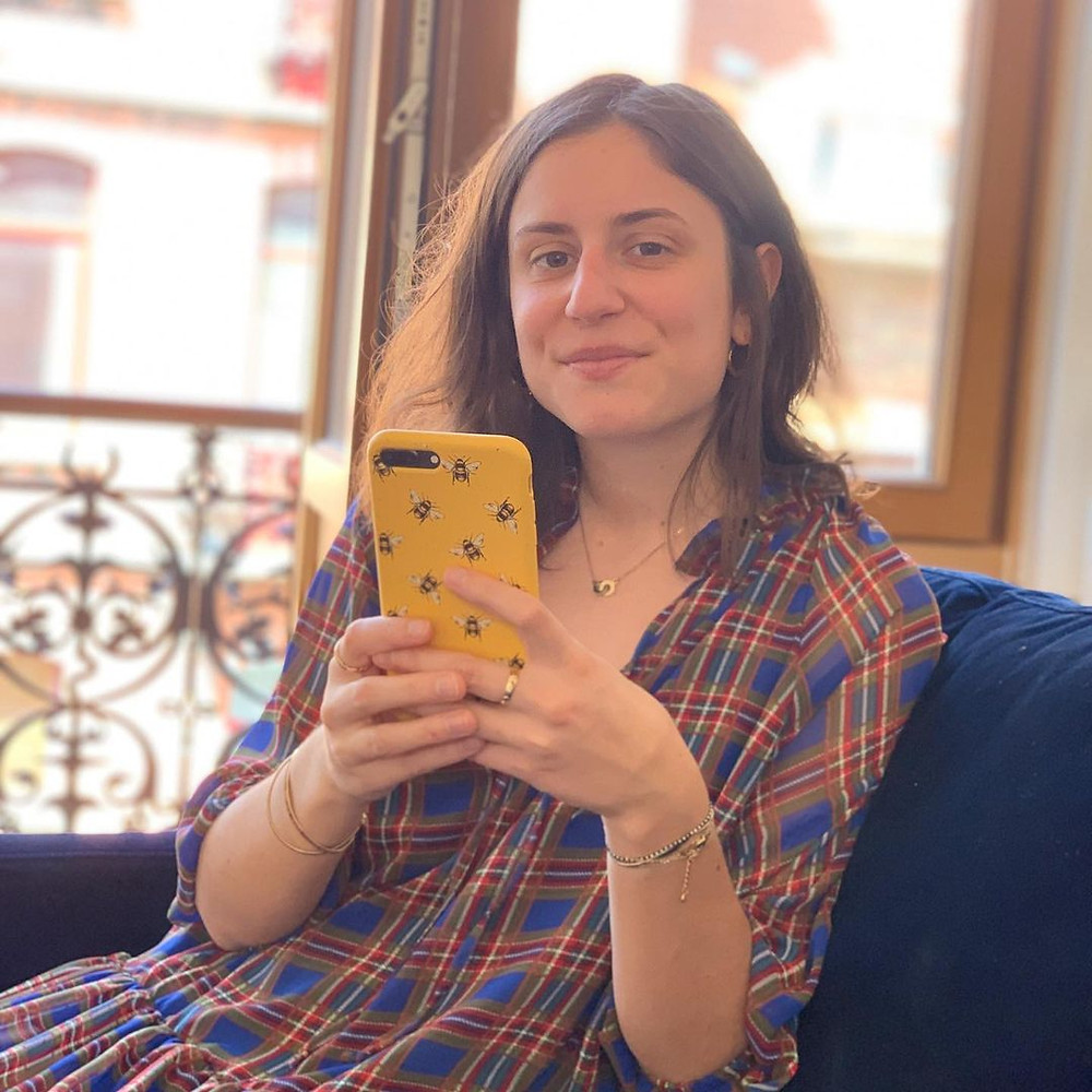 Conscious girl sitting in a sofa holding her phone