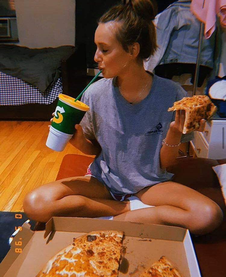 A girl sit in a bedroom eating pizza and drinking soda