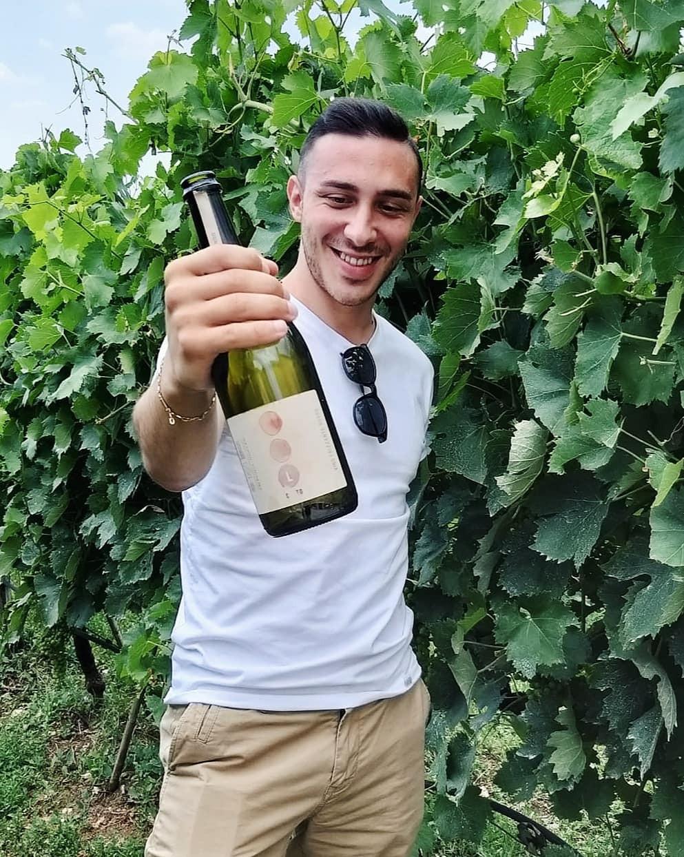 Ragazzo mostra bottiglia di vino