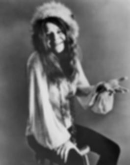 A photograph of Janis Joplin. She is sitting on a stool, smiling and gesturing with an open hand.