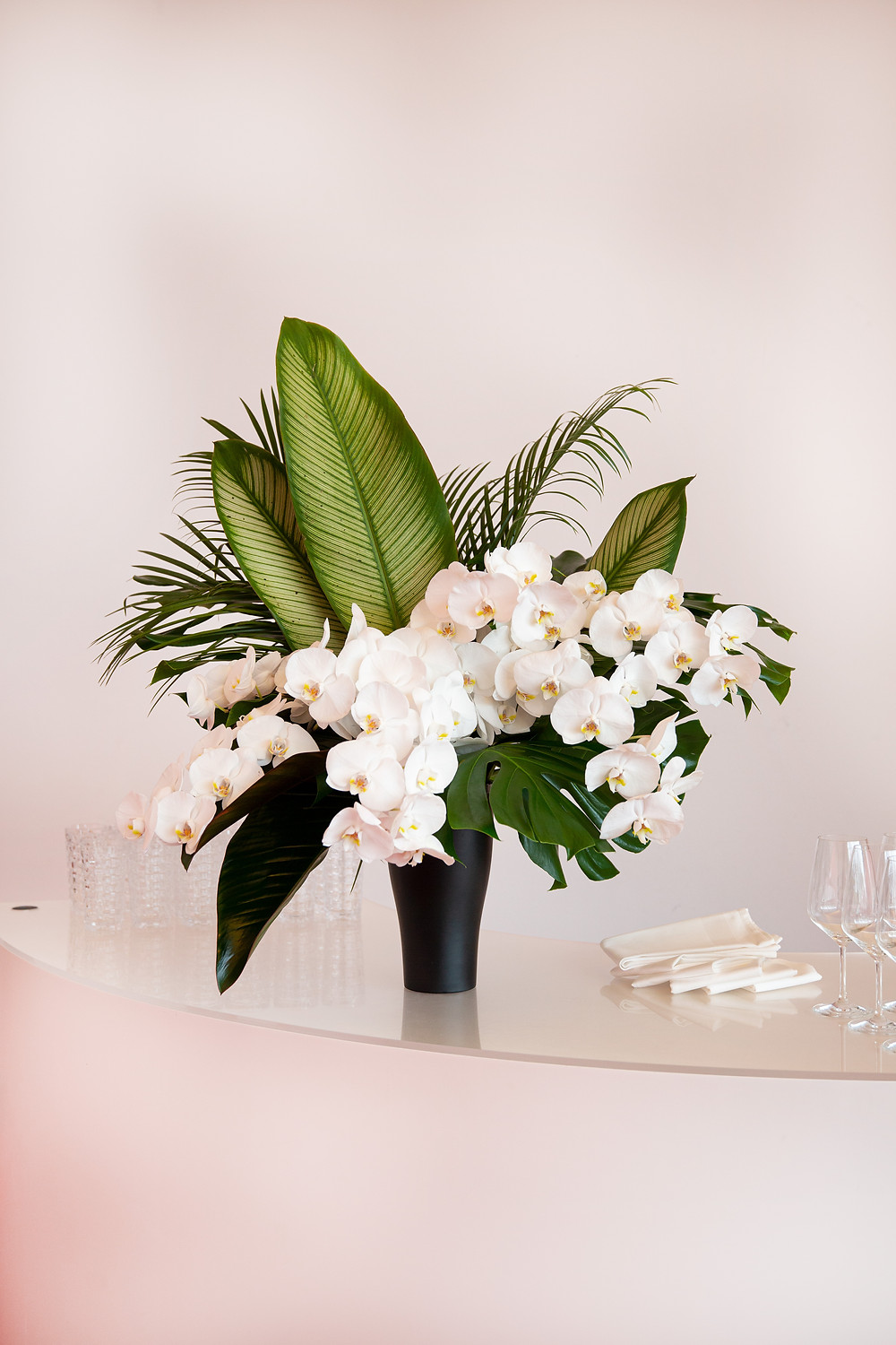 green and white floral arrangement with white orchids