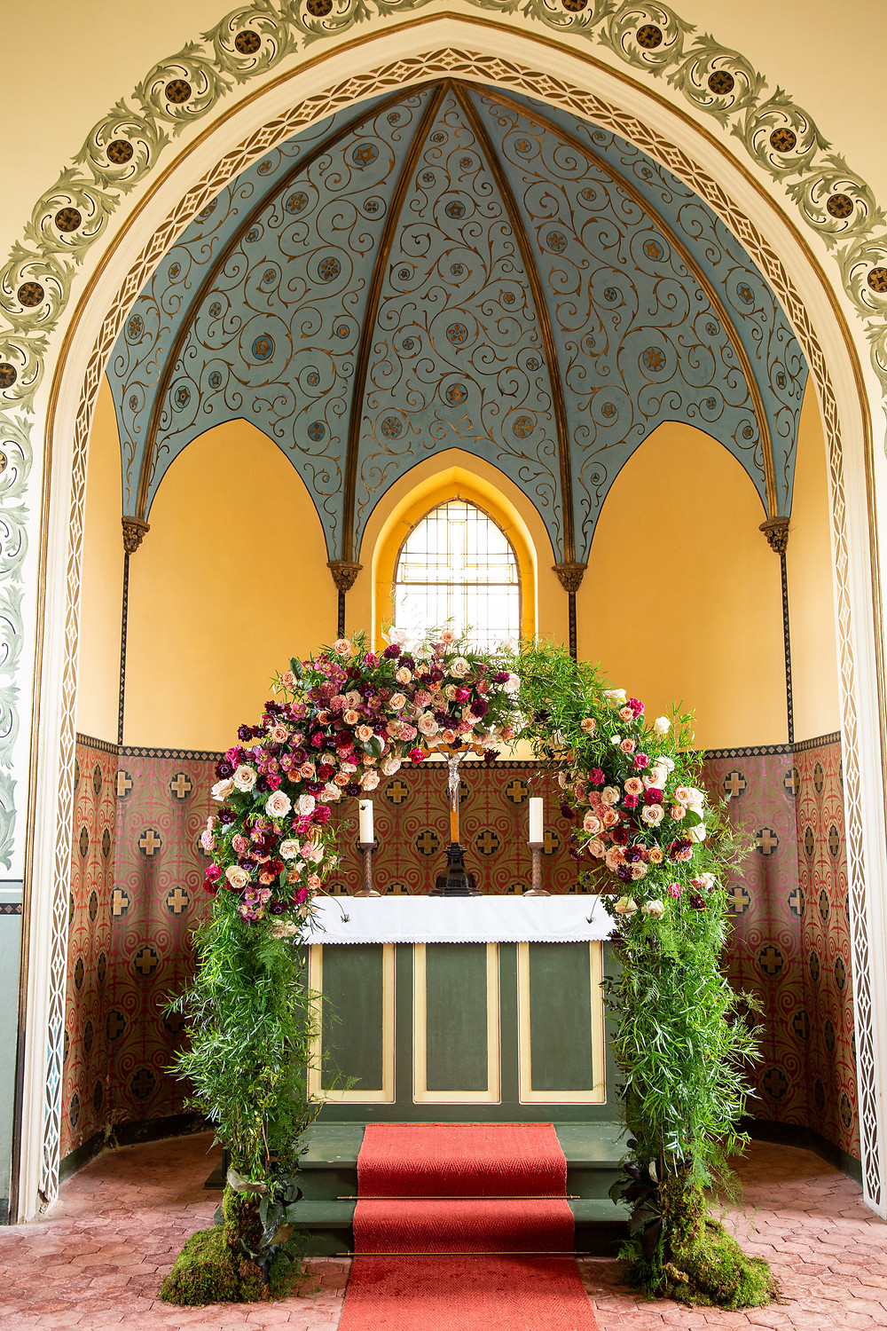 Floral arch using jewel tone flowers like roses, carnations and hellebores