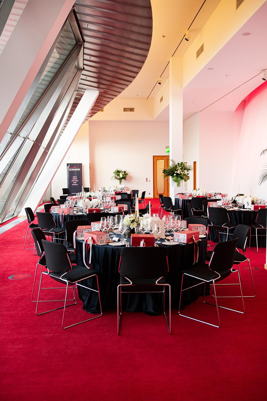 Corporate dinner setting with black velvet linens and white flowers