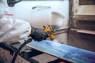 master-painter-factory-industrial-painting-wood-with-spray-gun.jpg