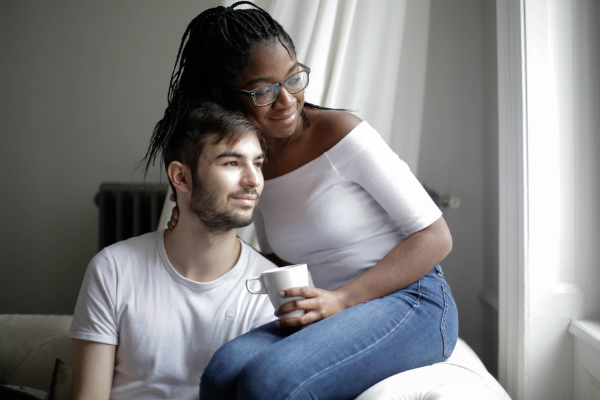 cheerful-multiethnic-couple-resting-on-s