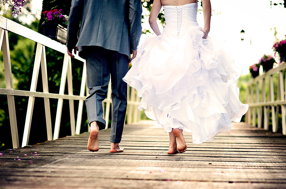 Newly wed couple walk barefoot across a bridge
