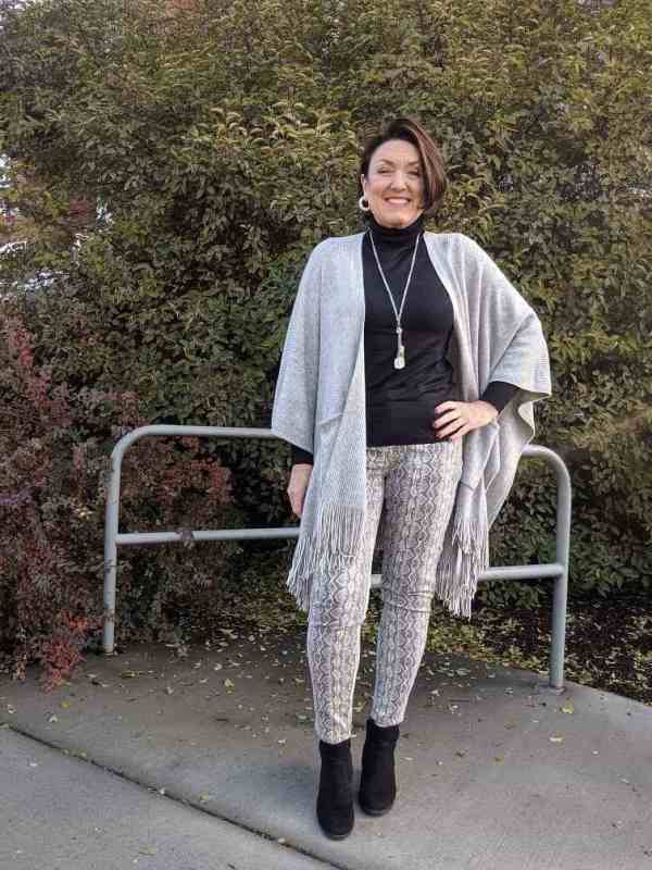 Grey knit fringe shawl and a pair of snake skin printed skinny jeans.