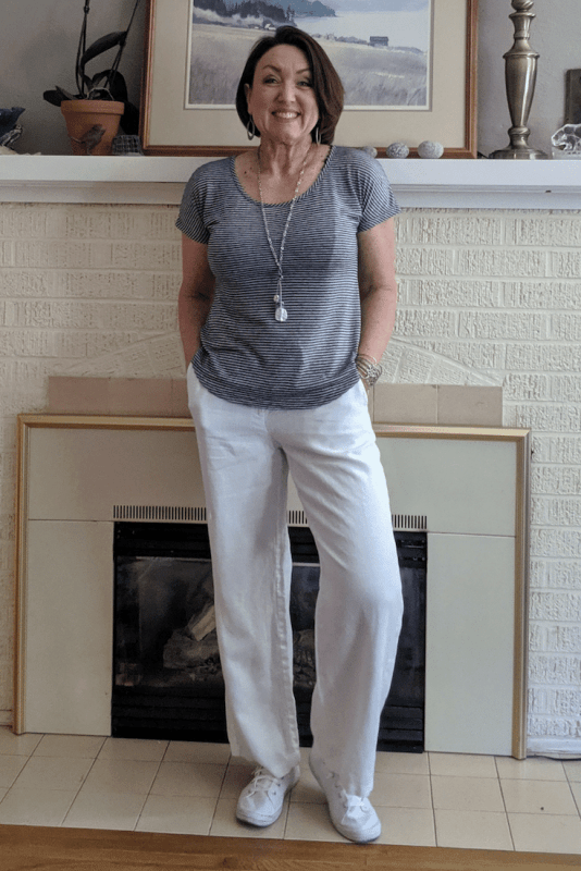White linen pants outfit for summer with slip on white tennis shoes and a striped t shirt.