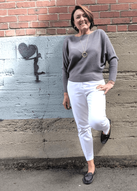 Wear white pants with a gray sweater to take them into fall and winter.