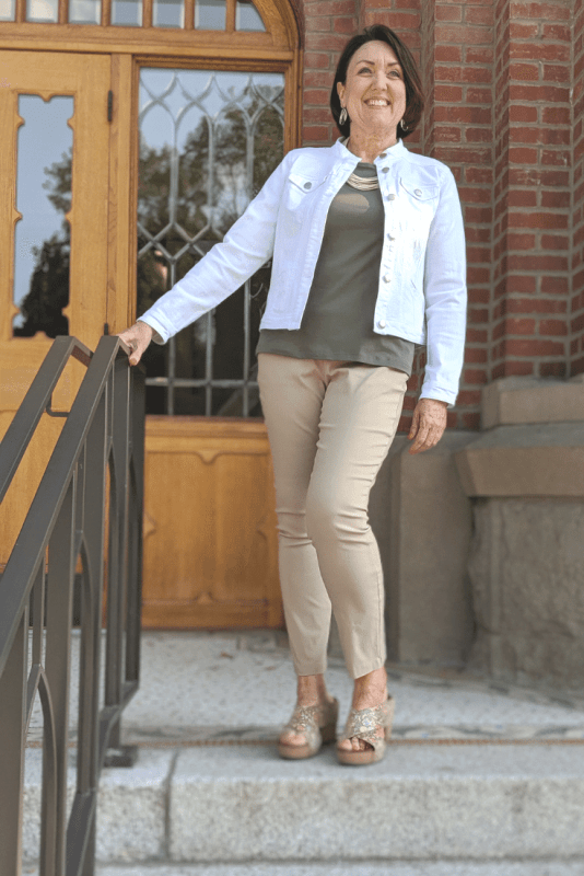 Swap out a white blazer for a white denim jacket over an olive green tank top and khaki ankle pants.
