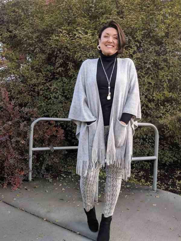 Fringe hem knit shawl with a black turtleneck and snake skin jeans.