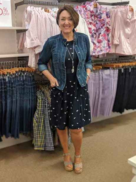 fitted blue jean jacket over a navy butterfly printed dress christopher and banks