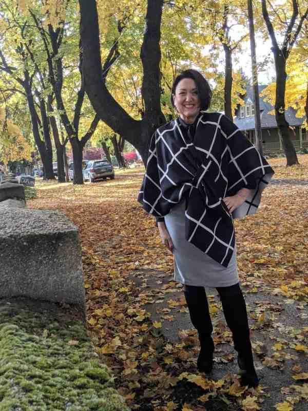 Reversible black and white check shawl over a pencil skirt and knee high boots