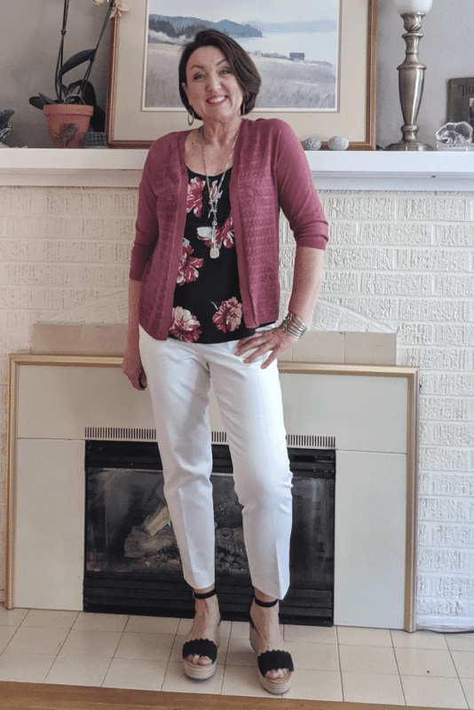 White work pant outfit with a soft rose colored cardigan and navy wedge sandals.