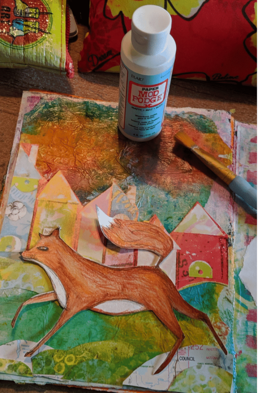 Mixed media fox art journal page using watercolors, colored pencils collage and inks.