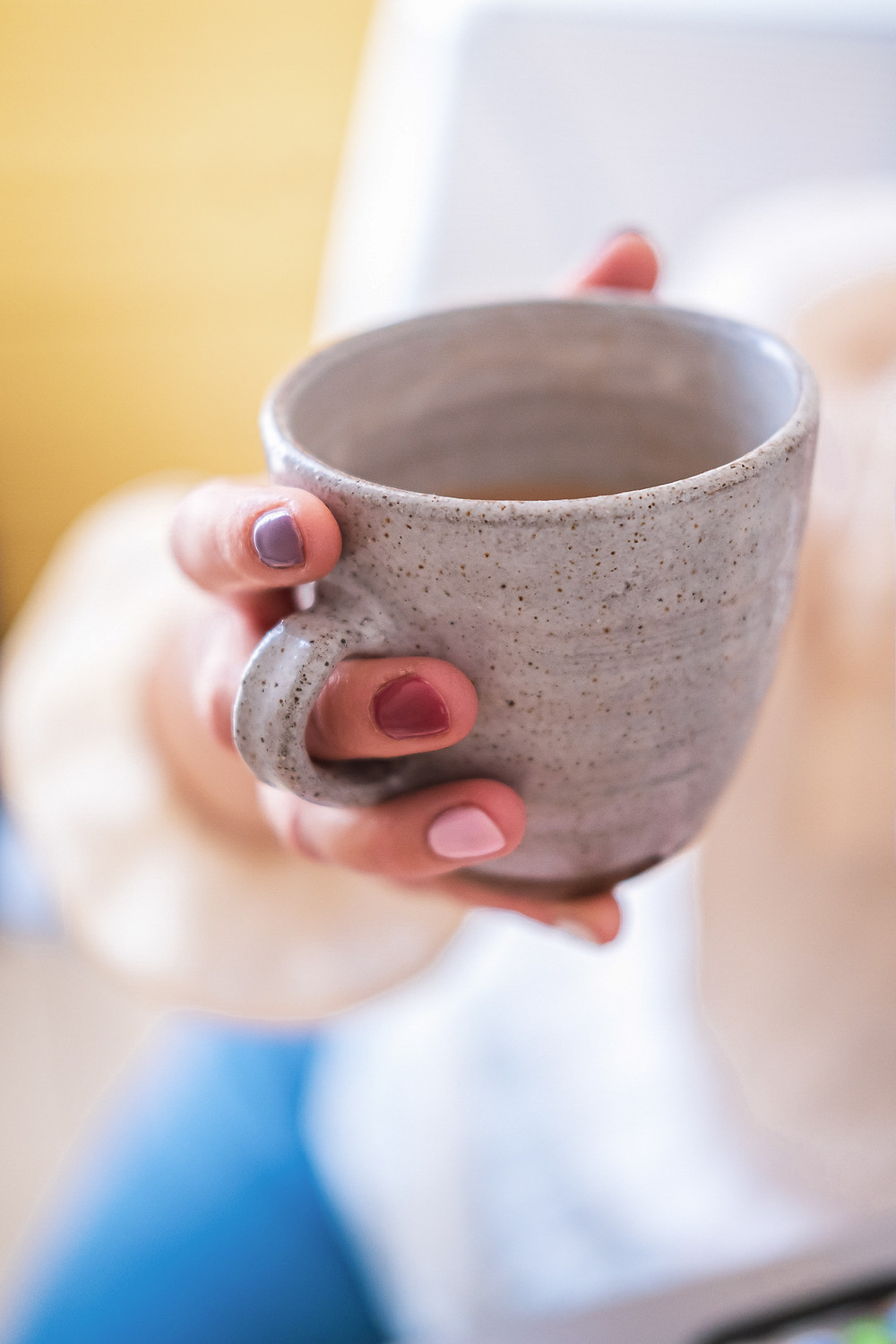Hannah Isted is holding a small handmade mug of tea in Barry