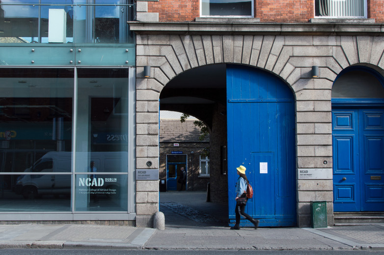 Woman walking to entrance to NCAD campus, Dublin, from Thomas Street
