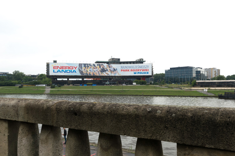 View across the Vistula River of the Forum Hotel (FORUM Przestrzenie) covered in a large advertisement in Krakow.
