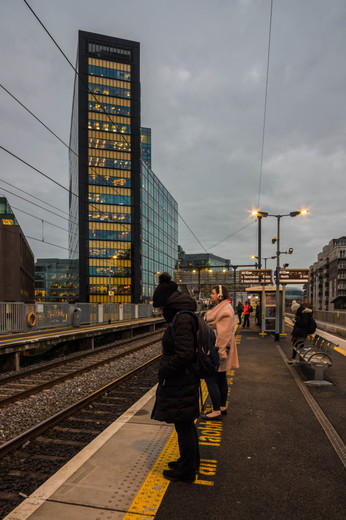 People waiting along track in front of Montevetro in Dublin at dusk
