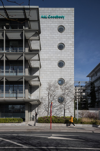 External view of granite clad facade with circular windows of A&L Goodbody Headquarters in Dublin from North Wall Quay