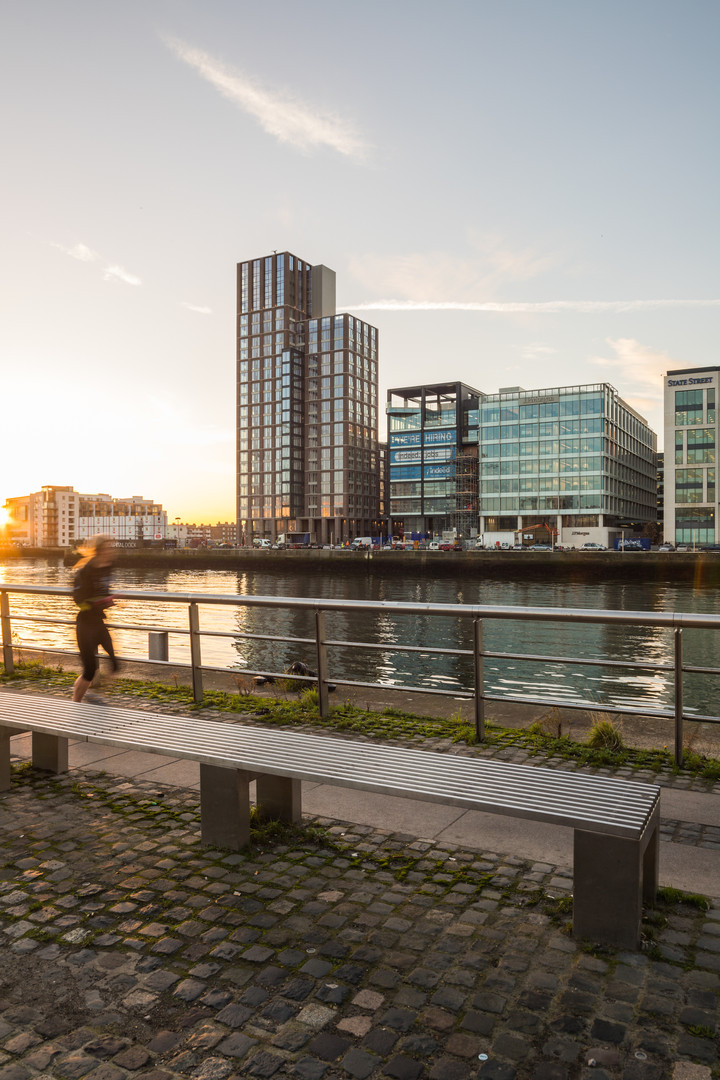 View of Capital Dock from across the Liffey with person jogging in Dublin