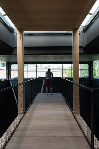 Person standing at end of timber bridge looking out window at Austria's pavilion at the Venice Biennale 2018