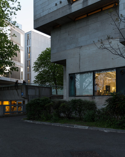 Granite clad exterior of the Ussher Library, Trinity College, Dublin at dusk in the background of the Berkeley Library