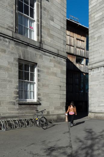 The oak clad Samuel Beckett Theatre viewed between two limestone buildings in Trinity College, Dubli