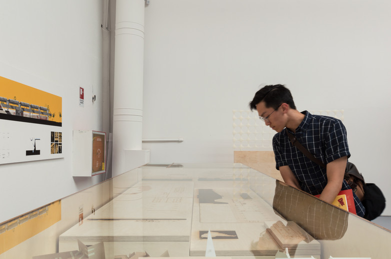 Man looking at drawings and models of Anhembi Tennis Club exhibition by Donaghy + Dimond at the Venice Biennale 2018