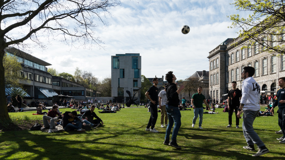 View across quad of Long Room Hub, Trinity College, Dublin, with students sitting and playing in foreground.