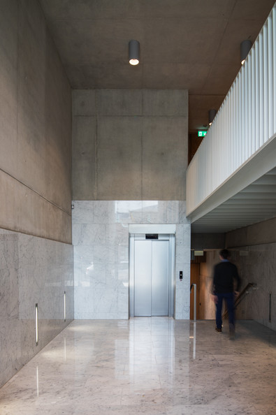 Interior entrance with bare concrete walls clad in white marble with white marble floors in the Hanging Gardens in Limerick