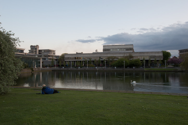 Man lying on grass with view across the lake of the Library at UCD, Dublin