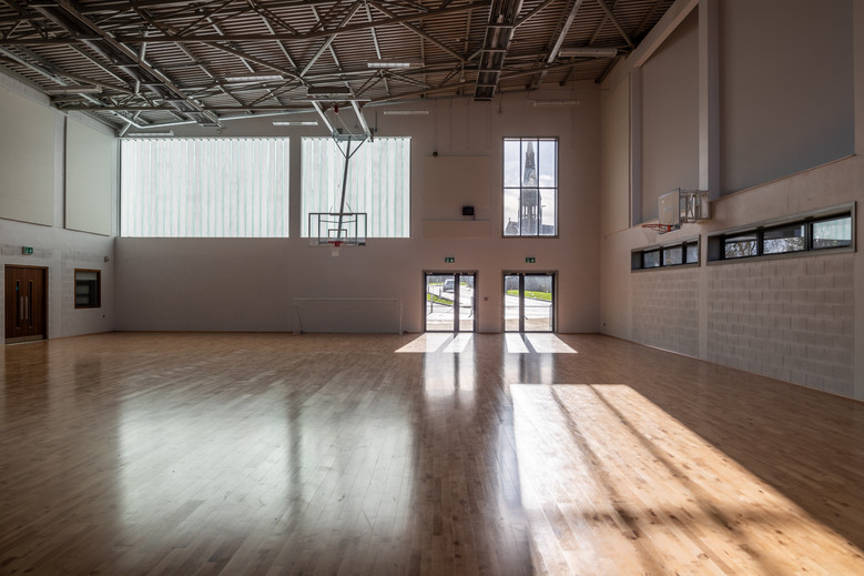 Interior of gym with view of St.Peter & Paul church through window in Colaiste Iosaef, Kilmallock, Limerick
