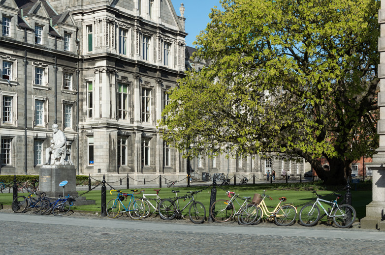 Bicycles parked along railing in front of quad surrounded by old limestone buildings inTrinity College Campus