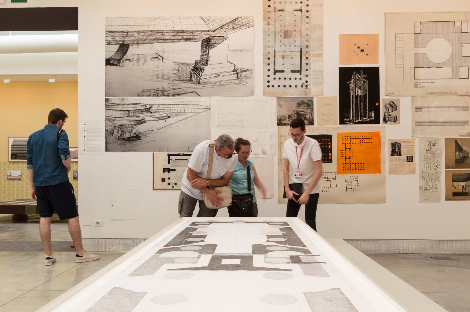 People looking at architectural drawings on a wall and table curated by Elizabeth Hatz Architects at the Venice Biennale 2018