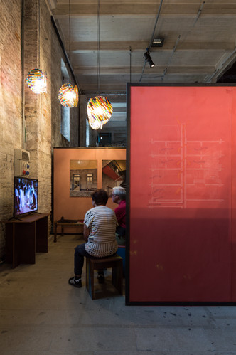 Two people sitting behind drawing watching video at the pavilion designed by Case Design at the Venice Biennale 2018